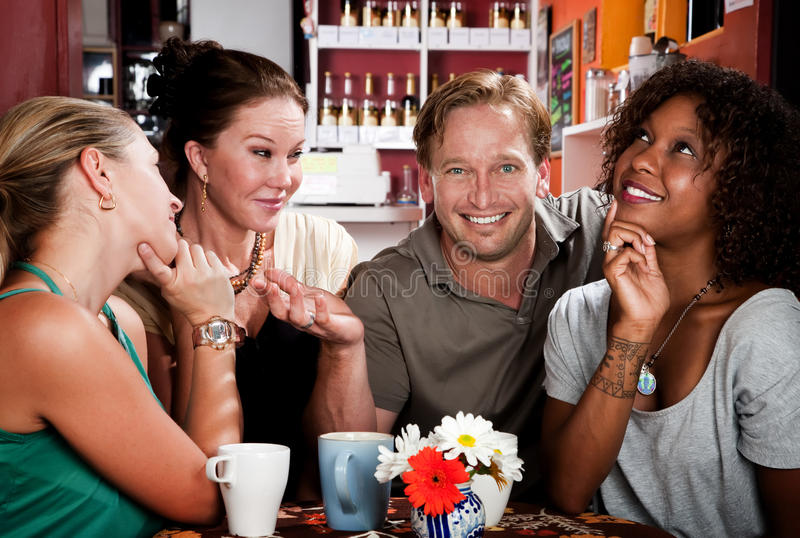 Man with three pretty women in coffee house royalty free stock images