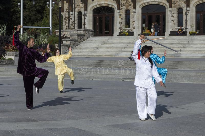 Man and three women in Asian outfits participating in a Tai Chi demonstration stock image