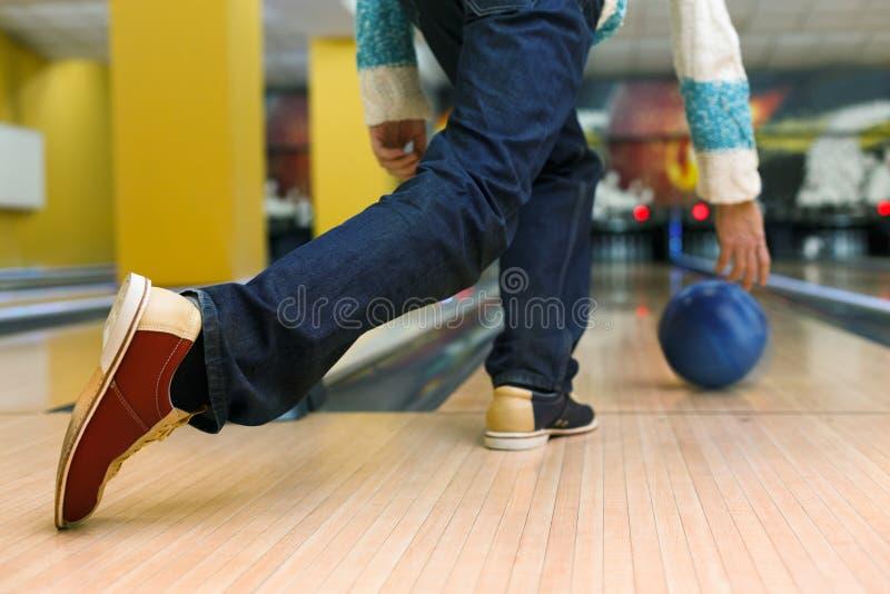 Man throw ball at bowling lane, cropped image. Unrecognizable man throw ball to bowling lane, closeup. Player plays active game, making strike. Cropped image of royalty free stock images