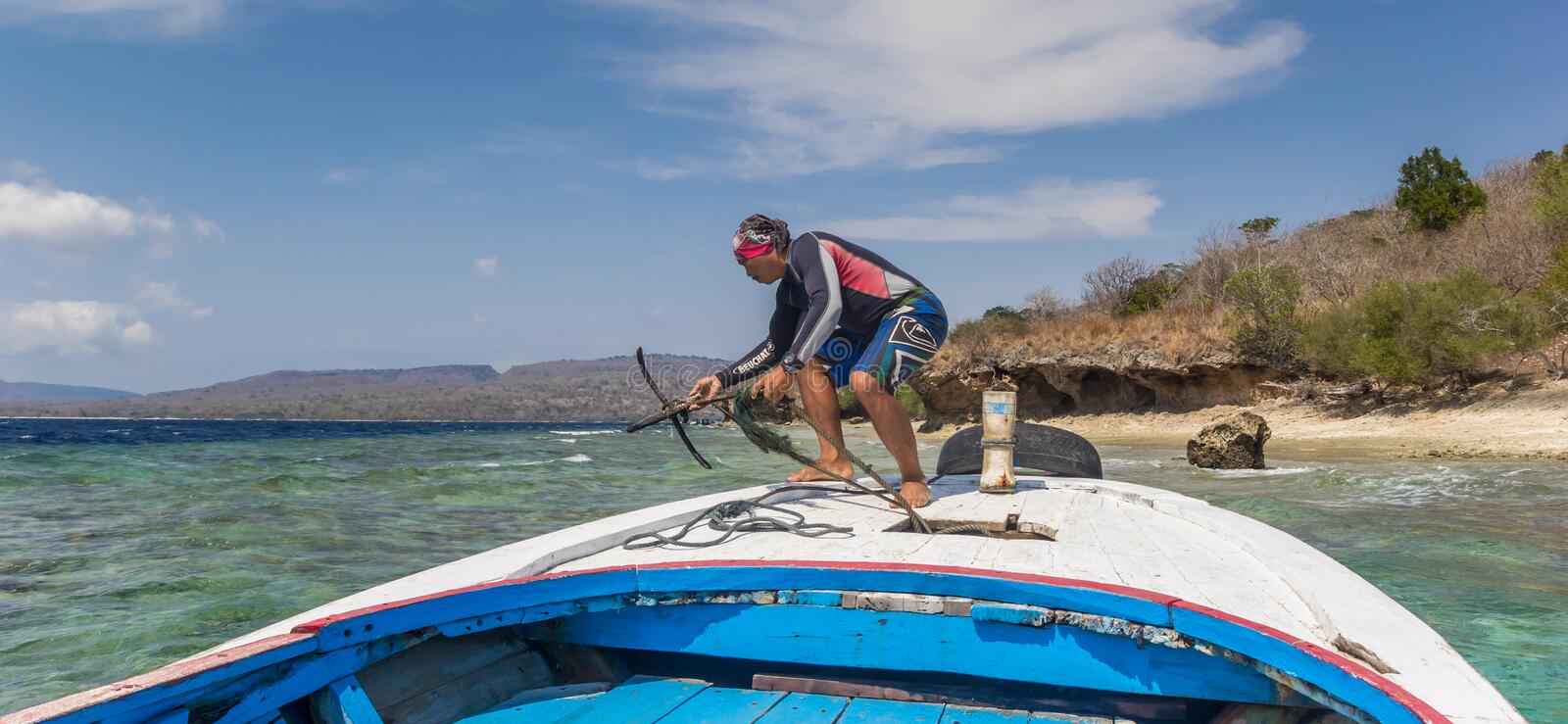 Man throwing an anchor from the bow of a wooden boat. At the coast of Menjangan Island stock images