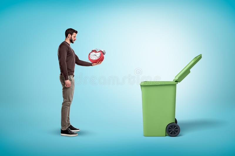 Man throwing broken red clock into open trash bin on blue background. Digital art. People and objects. Trash and garbage stock photography