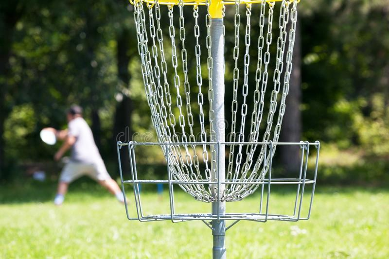 Man throwing frisbee playing disc golf in the park. Man playing disc golf in the park royalty free stock photography