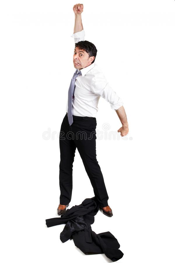 Man throwing his jacket down. Mature businessman throwing his jacket down on the floor in frustration and anger and raising his fist in the air belligerently stock images
