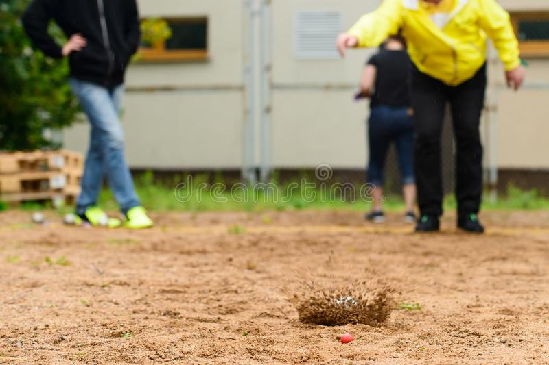 Man throwing metal ball for petanque game on sand. Man throwing metal ball for petanque game on the sand stock photography