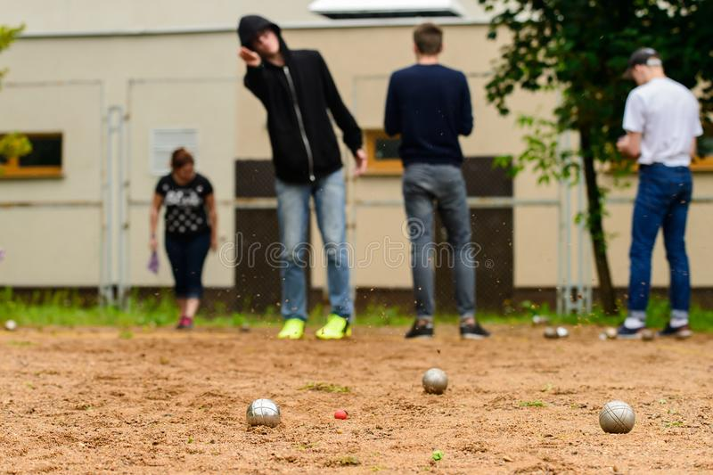 Man throwing metal ball for petanque. Game on the sand stock photography