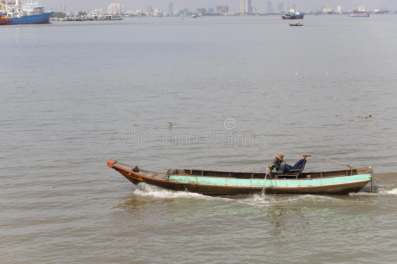 Man throwing out water from his boat on the Saigon river royalty free stock photos