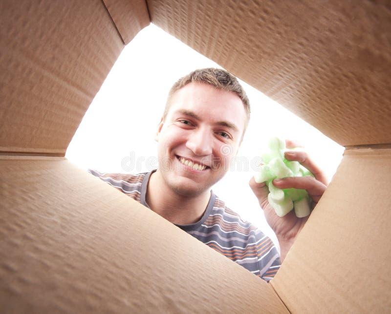 Man throwing packing polyfoam into cardboard box royalty free stock photos
