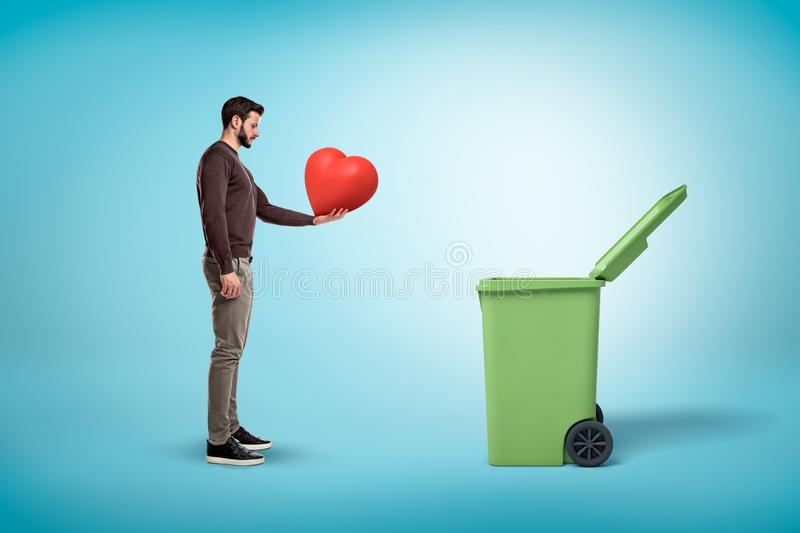 Man throwing red heart into open garbage bin on blue background. Digital art. People and objects. Trash and garbage stock photography
