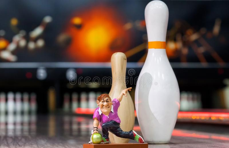 Toy man throws a ball on the background of bowling, a man playing bowling. A man throws a ball against the background of bowling, the toy layout stock photo