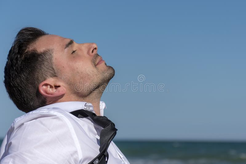 Man with tie and white shirt sunbathing on his face stock photo