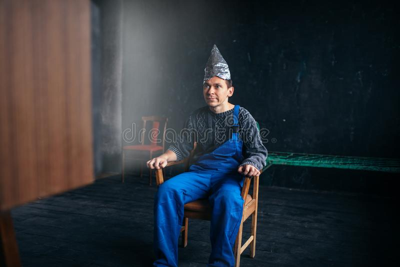 Man in tinfoil hat sits in chair, paranoia concept stock image