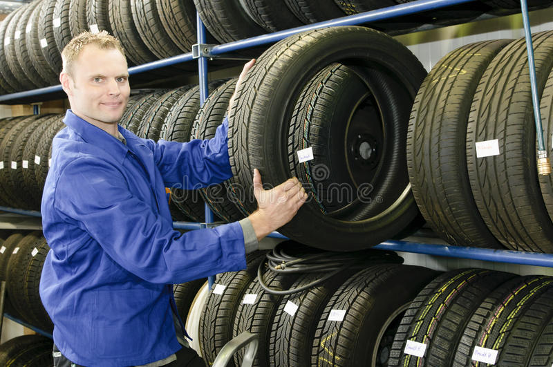 Man in the tire store with a tire stock image