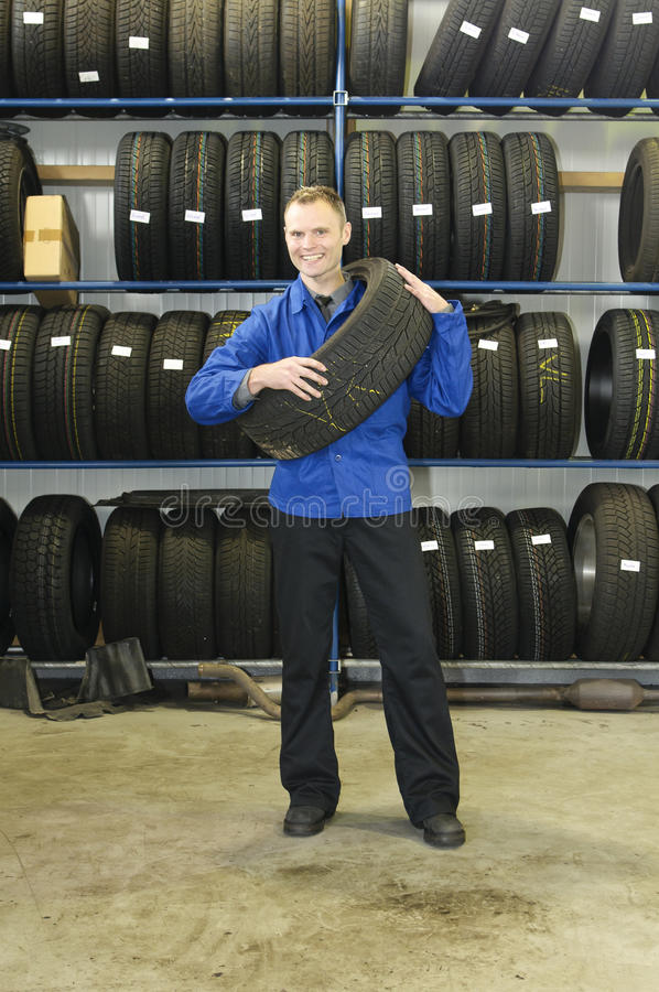 Man in the tire store with a tire, royalty free stock photography