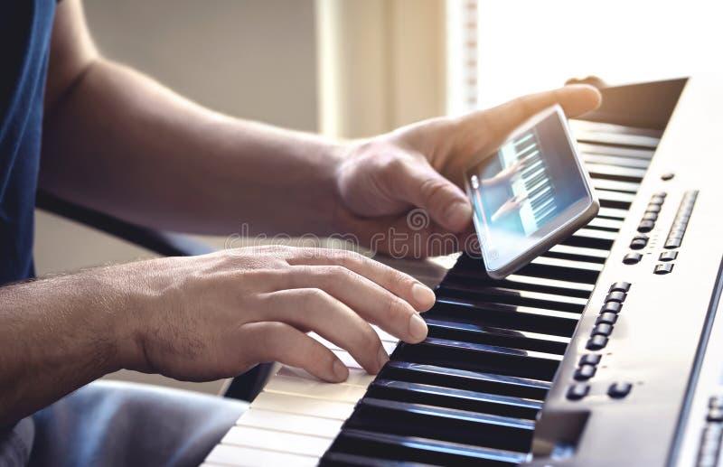 Man tittar på självstudievideo i piano med mobiltelefon Person som leker med en lektion och kurs online royaltyfria foton