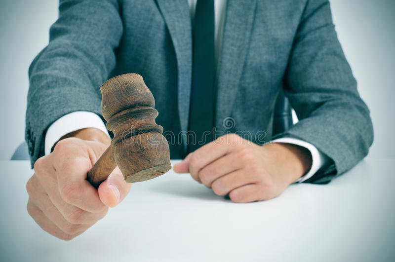 Man about to struck a gavel. Closeup of a man in suit about to struck a gavel stock image