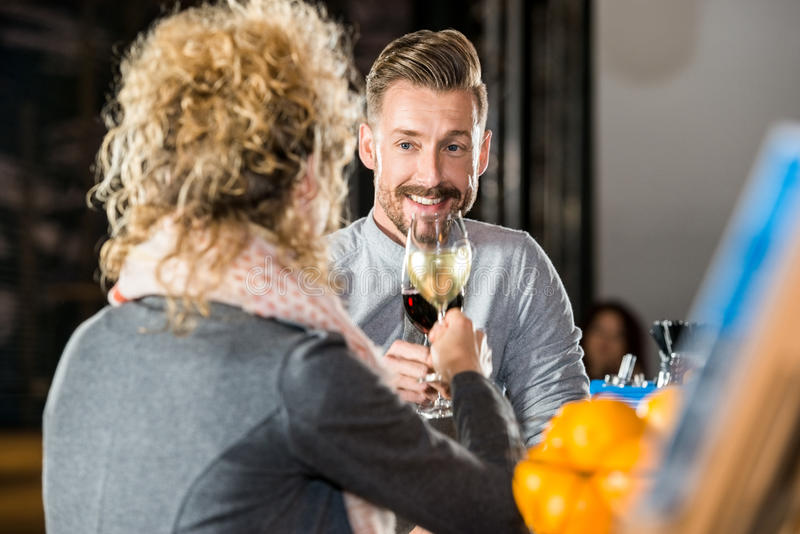Man Toasting Wine With Friend In Bar. Young men toasting wine with female friend in bar stock photo