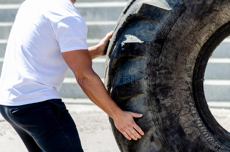 Man moves a huge wheel of industrial machines. Man tolkae a huge wheel of industrial machines stock image