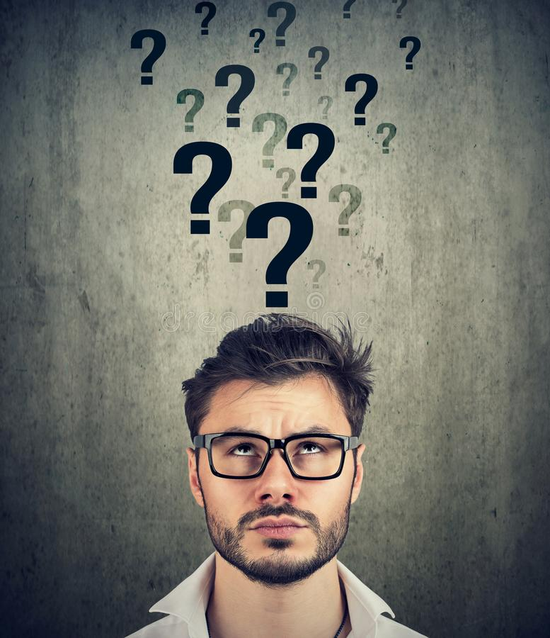 Man with too many questions and no answer. Perplexed young man with too many questions and no answer stock images