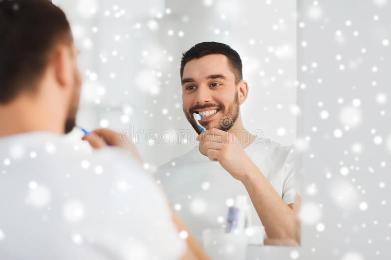 Man with toothbrush cleaning teeth at bathroom. Health care, dental hygiene, people and beauty concept - smiling young man with toothbrush cleaning teeth and stock images