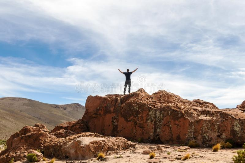 Man on the top of the cliff with hands up royalty free stock image