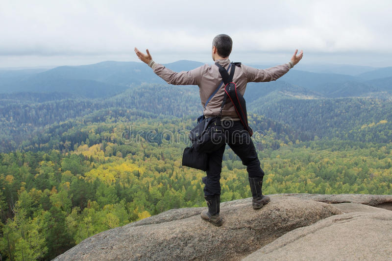 The man at top of the mountain enjoys beauty of the nature. To achieve the objectives. The man at top of the mountain enjoys beauty of the nature. To achieve the stock image