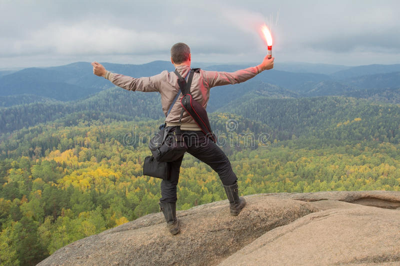 The man at top of the mountain enjoys beauty of the nature. To achieve the objectives. The man at top of the mountain enjoys beauty of the nature. To achieve the stock photo