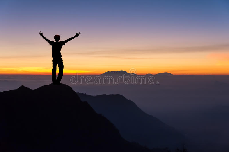 Man on top of the mountain looking to the sunrise. Man on top of the mountain spread hand and looking to the sunrise stock photos