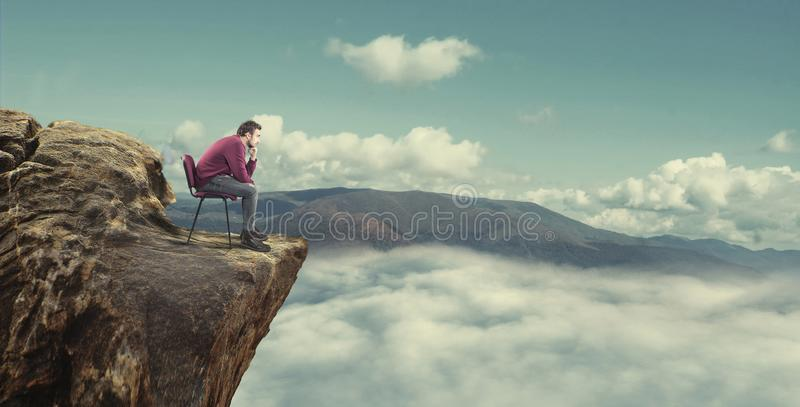Man is at the top of the mountain. Thoughtful man sitting on chair at the top of the mountain and looking to horizon royalty free stock photography