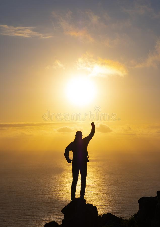 Man on top of the mountain watching the sunset over the sea, Basque Country stock photo