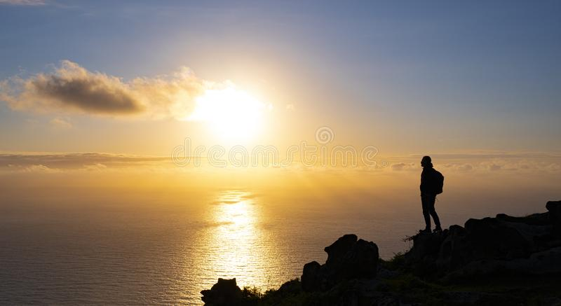Man on top of the mountain watching the sunset over the sea, Basque Country stock images