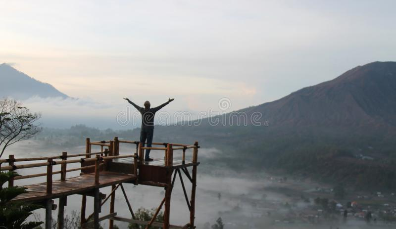 Man on top of mountain. Young man standing on the height of a wooden bridge, raised hands & open arms against mountain scenery. stock photo