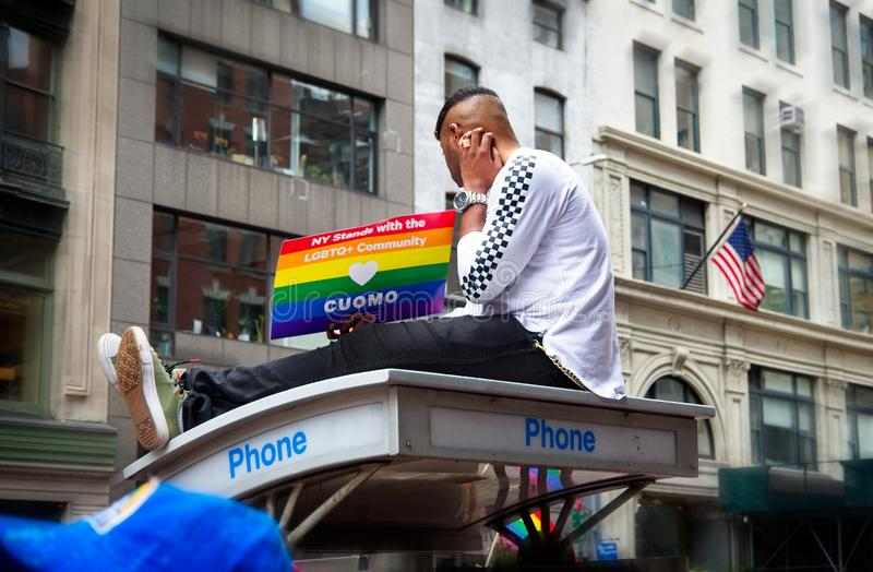 Man on top of phone booth holding a sign at the 2018 New York City Pride Parade stock images