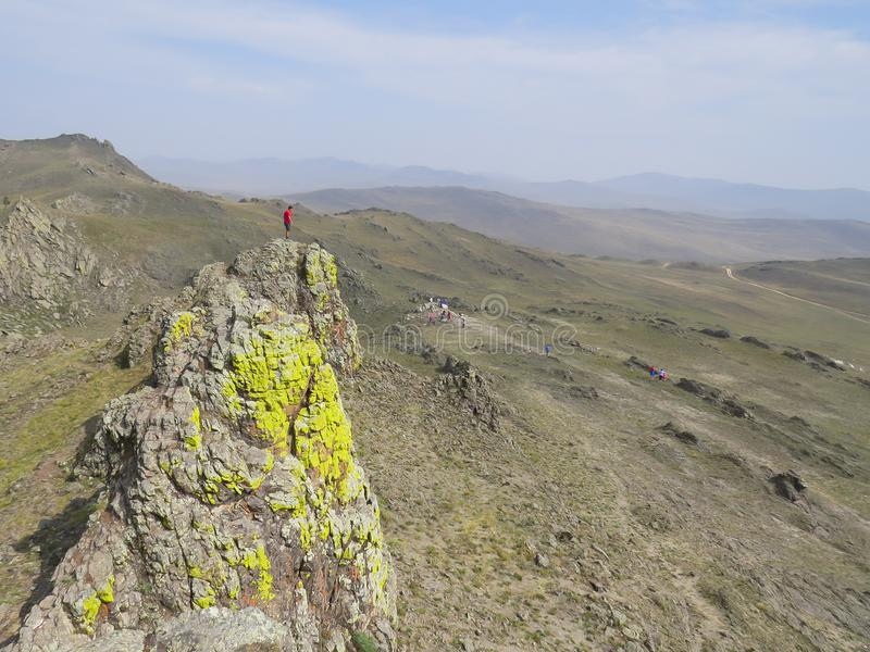 A man on top of a rock covered with lichen. The castle of Spirits. Is a place of power of Olkhon island, lake Baikal royalty free stock images