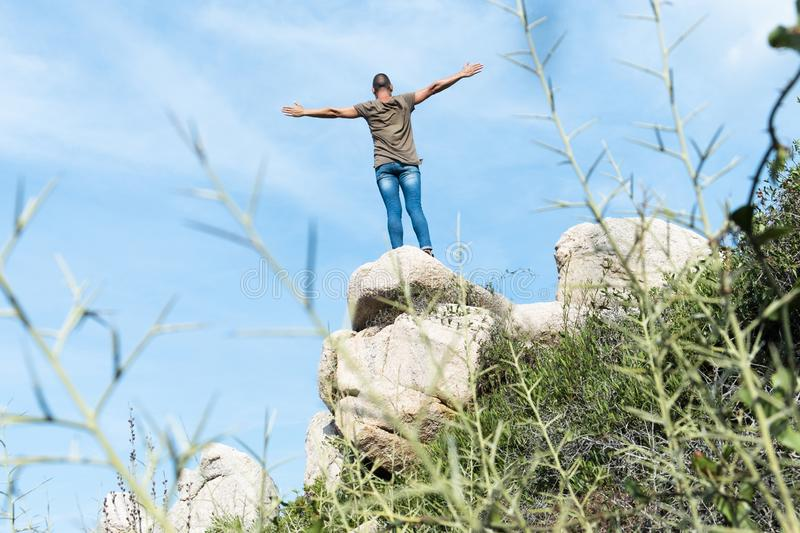 Man on the top of a rock formation with his arms in the air. A young caucasian man, wearing a green T-shirt and jeans, seen from behind, feeling free on the top stock photos