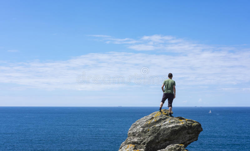 Man on top of rock, looking at sea stock photo