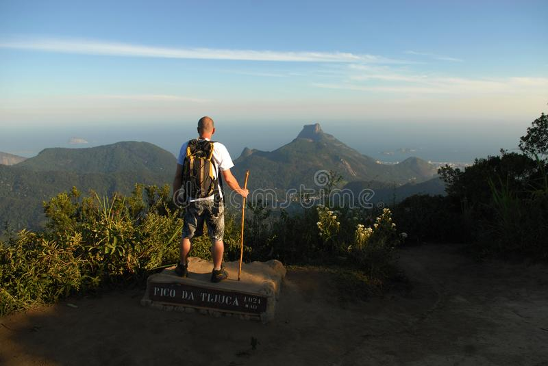 Man at the top of Tijuca Peak. Rio de Janeiro, Brazil, March 30, 2018. Man in the top of Pico da Tijuca, inside the Tijuca National Park observes the view of stock photography