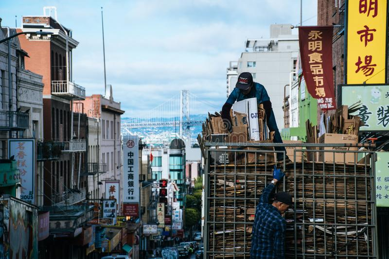 Man on Top of Truck Arranging Brown Cardboard Boxes stock photo