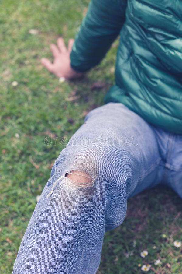 Man with torn jeans on grass. A trendy young man with a hole torn in his jeans at the knee is sitting on the grass royalty free stock photo