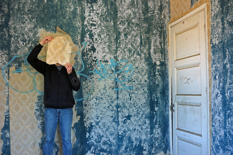 Man with torn wallpaper. Shred in decayed blue room abandoned house interior stock image