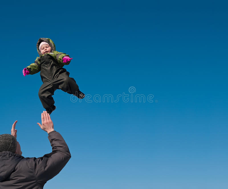 Man tossing up a child royalty free stock image