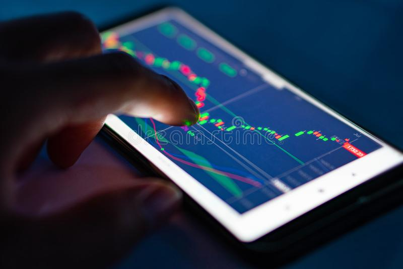 Man touch candlestick chart from stock market on smartphone royalty free stock images