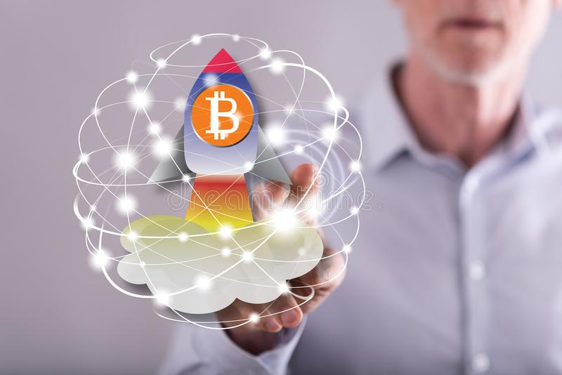 Man touching a bitcoin rise concept on a touch screen. With his finger stock photography