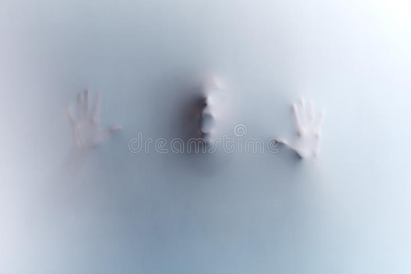 Man touching the glass, leaning on it, expressing negative feeling, emotion stock image