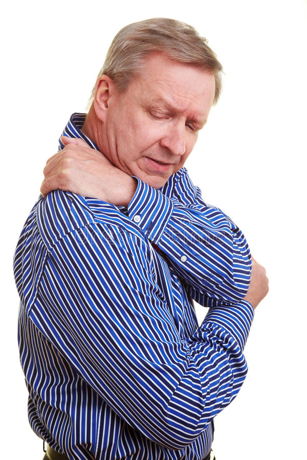 Man touching his aching shoulder. Elderly man holding hands to his aching back stock image