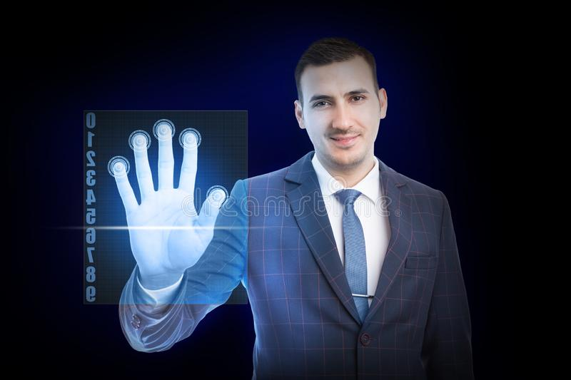 Man touching screen with fingers. Smiling man wearing suit and tie touching transparent screen with fingers for recognition as futuristic concept on blue royalty free stock photo