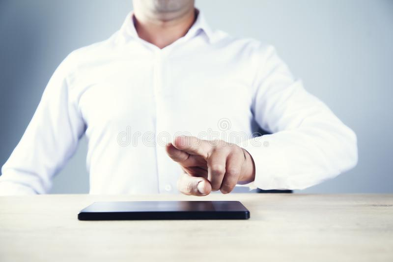 Man touching in screen with tablet. In office stock photos