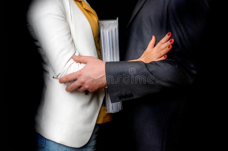 Man touching woman`s elbow - sexual harassment in office. Man touching woman`s elbow isolated on black - sexual harassment in business office stock photography
