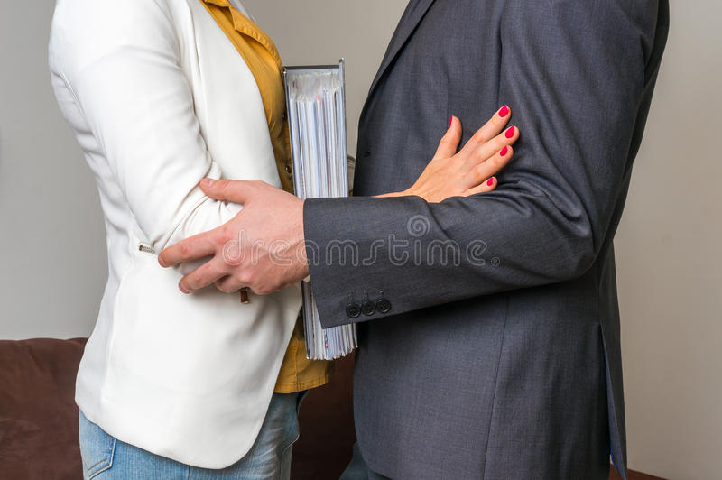 Man touching woman`s elbow - sexual harassment in office. Man touching woman`s elbow - sexual harassment in business office royalty free stock image