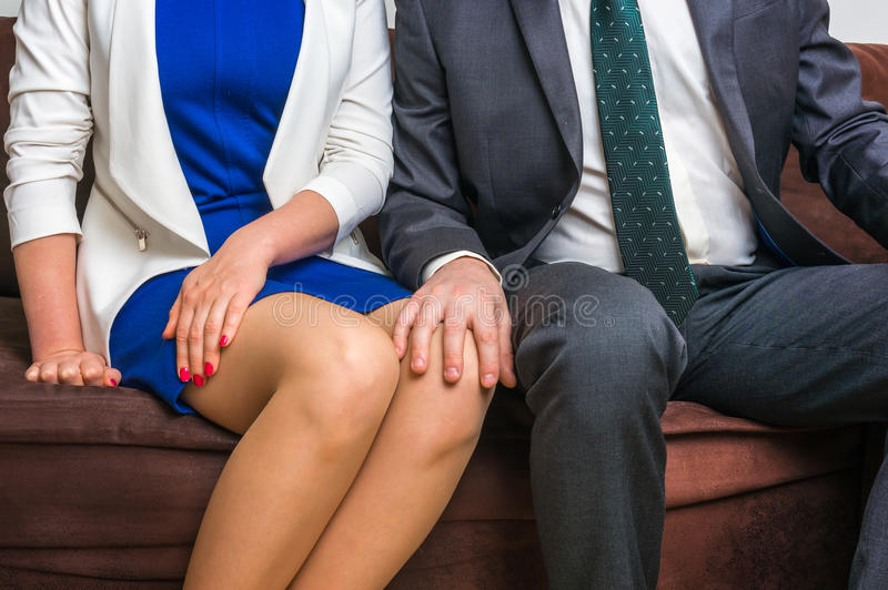 Man touching woman`s knee - sexual harassment in office. Man touching woman`s knee - sexual harassment in business office stock image