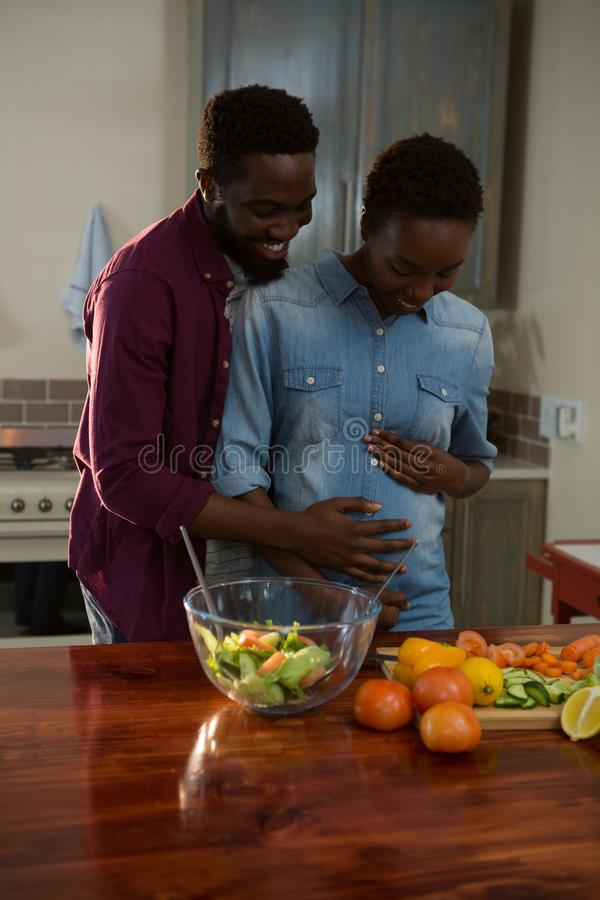 Man touching womans pregnant belly in the kitchen. At home stock image